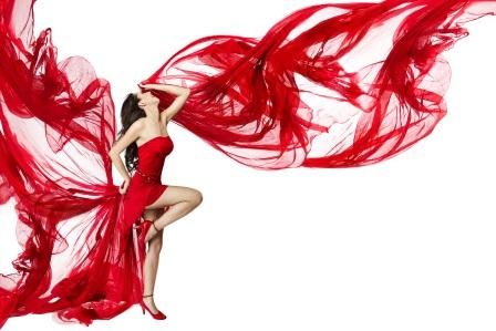 Beautiful woman dancing in red dress flying on a wind flow over white background